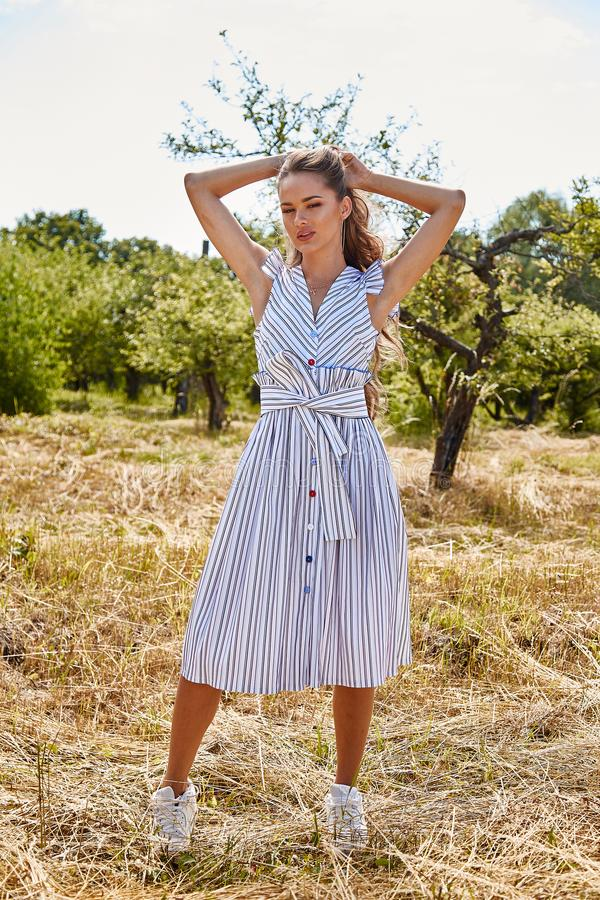 Beautiful young woman long hair bright makeup nature backgr. Ound landscape dry spike grass and apple trees garden summer model wear in light white cotton dress royalty free stock image