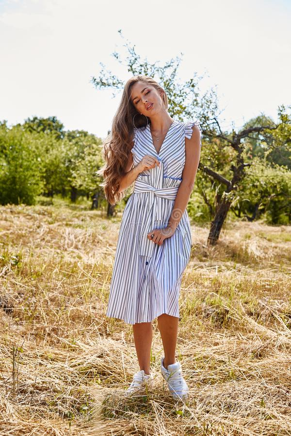 Beautiful young woman long hair bright makeup nature backgr. Ound landscape dry spike grass and apple trees garden summer model wear in light white cotton dress stock images