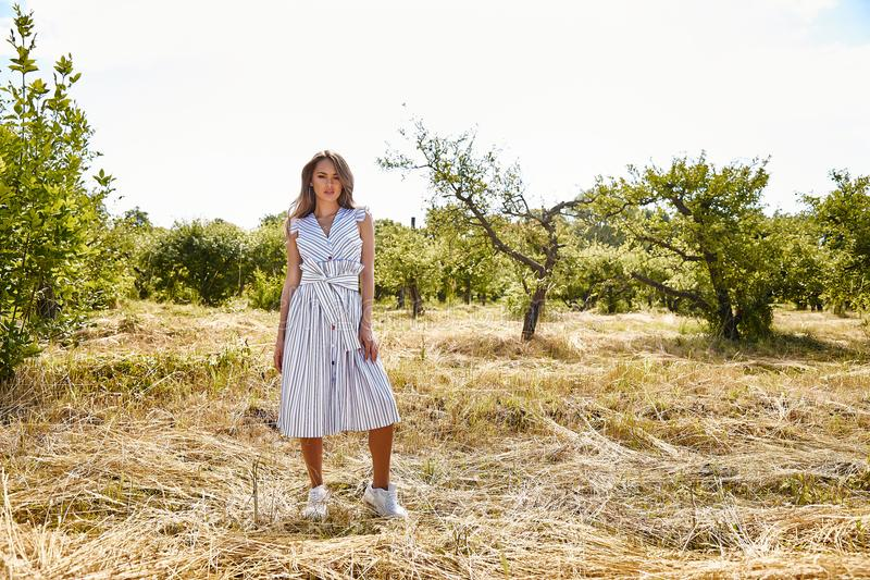 Beautiful young woman long hair bright makeup nature backgr. Ound landscape dry spike grass and apple trees garden summer model wear in light white cotton dress stock photo
