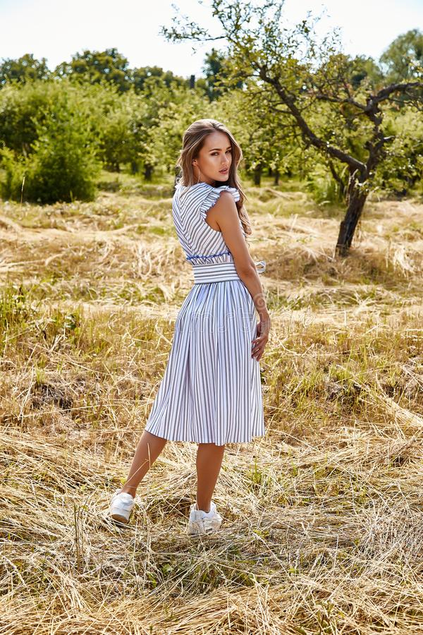 Beautiful young woman long hair bright makeup nature backgr. Ound landscape dry spike grass and apple trees garden summer model wear in light white cotton dress royalty free stock photo