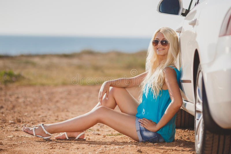 Beautiful young woman near a car outdoor. Beautiful young woman near car outdoor. Rich hot blond slim girl with long healthy hair posing with luxury expensive royalty free stock photos