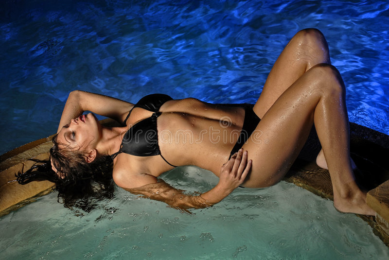Beautiful young woman at poolside stock photo