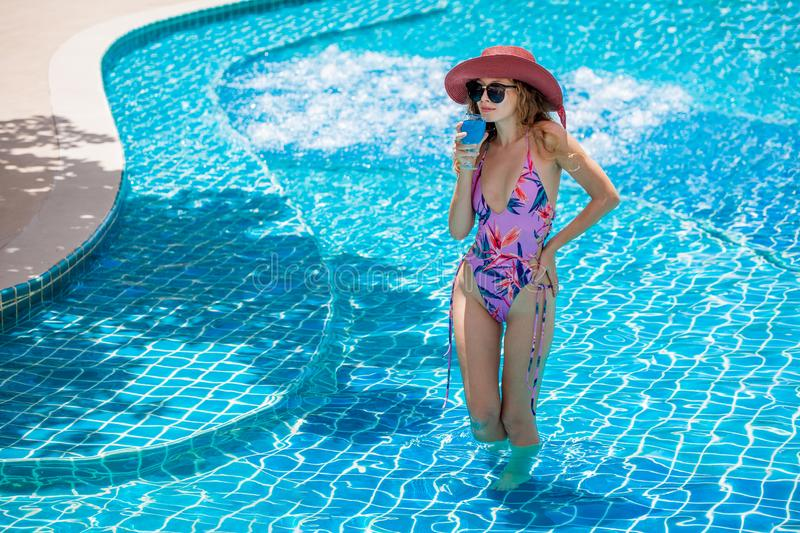 beautiful Young sexy woman wearing bikini with sunglasses and red hat drinking cocktail in swimming pool. Pretty girl in swimsuit royalty free stock photography