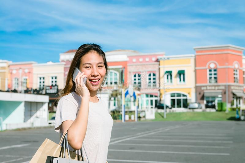 Beautiful young shopaholic Asian woman using smartphone for talking while she walking to buy cosmetics, clothes etc. stock images