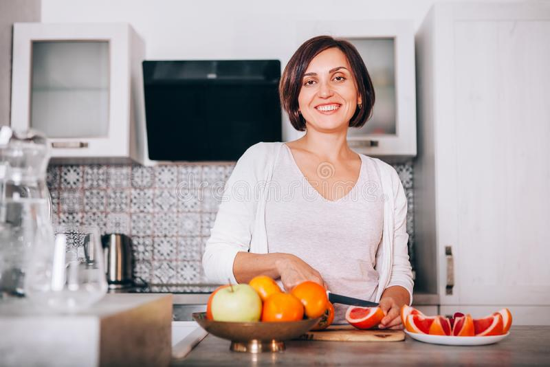 Beautiful young sincerely smiling female chopping grapefruit using a knife and cutting board in modern kitchen. Plenty of apples, stock images