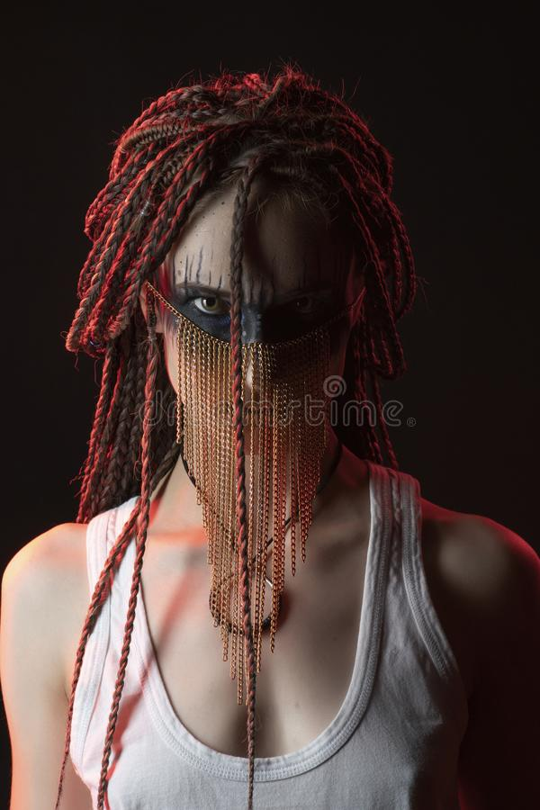 Beautiful young slim girl with a creative make-up and hairstyle of cornrows, dressed in a white T-shirt and jewelry of gold chains. On her face. Conceptual stock photo