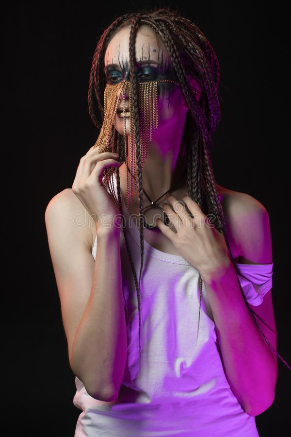Beautiful young slim girl with creative make-up and a hairstyle of cornrows, wearing white t-shirt and jewelry of gold chains on. Her face. Conceptual stock images