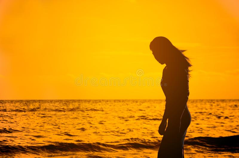 Beautiful young slim girl standing on sandy beach. At sea at the sunset stock photography