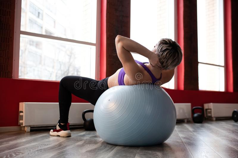 Beautiful young slim woman doing some gymnastics at the gym with fitball royalty free stock photos