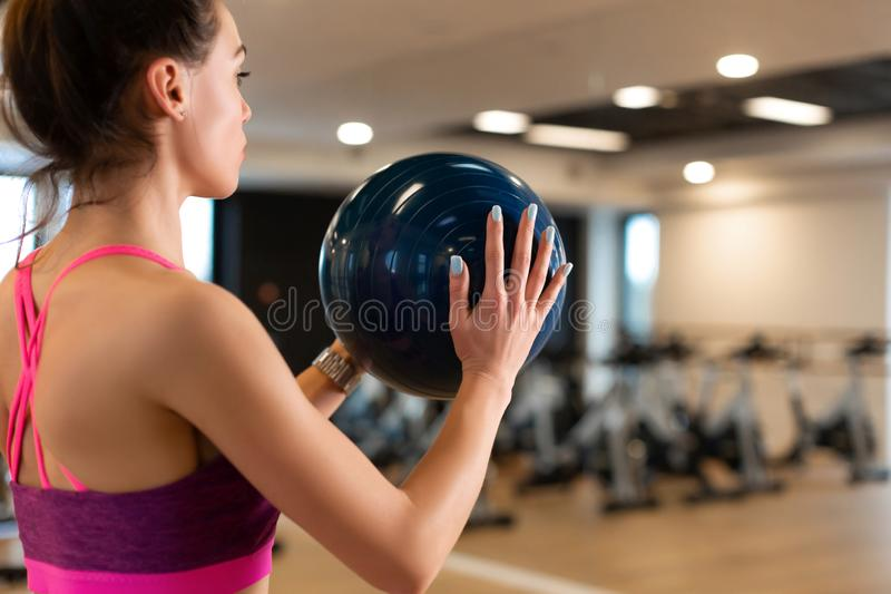 Beautiful young slim woman in sportwear doing some gymnastics at the gym with medball royalty free stock photos