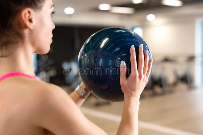Beautiful young slim woman in sportwear doing some gymnastics at the gym with medball royalty free stock photo