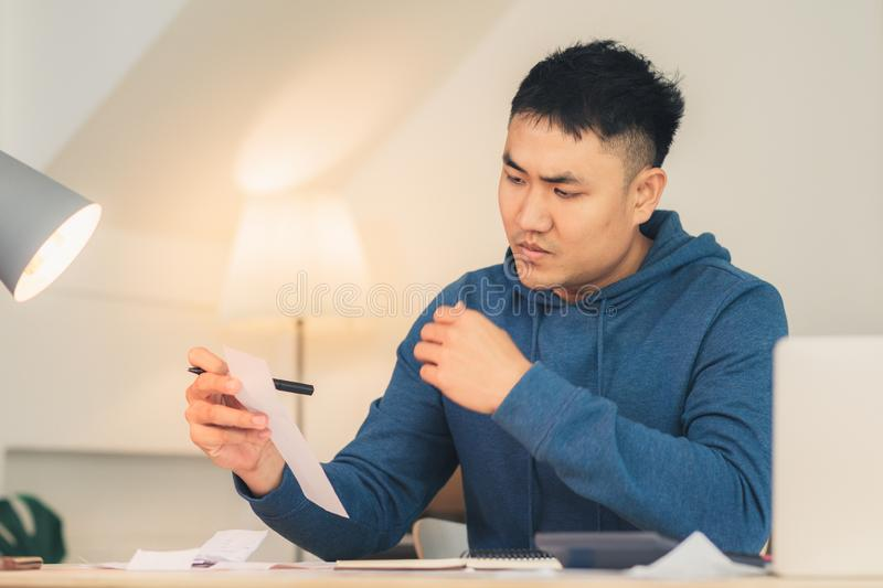 Beautiful young smiling asian man working laptop on desk in living room at home. Asia business man writing notebook document finance and calculator in home royalty free stock photo