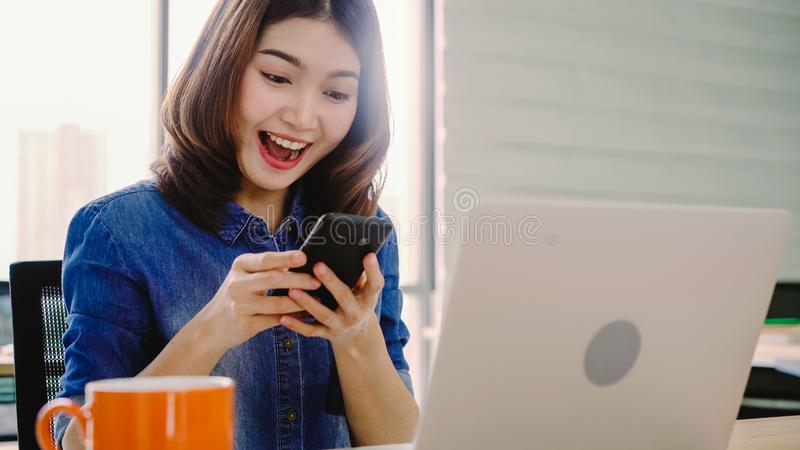 Beautiful young smiling asian woman working on laptop while enjoying using smartphone at office royalty free stock photos