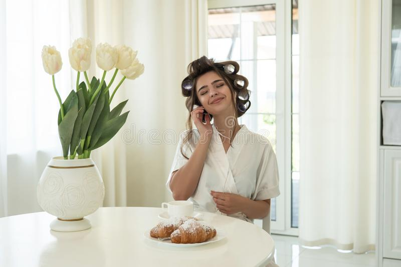 Beautiful young smiling brunette in hair curlers enjoying music while having breakfast in bright kitchen stock image