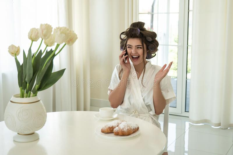 Beautiful young smiling brunette woman in hair curlers speaking on smartphone while drinking coffee and eating stock photos
