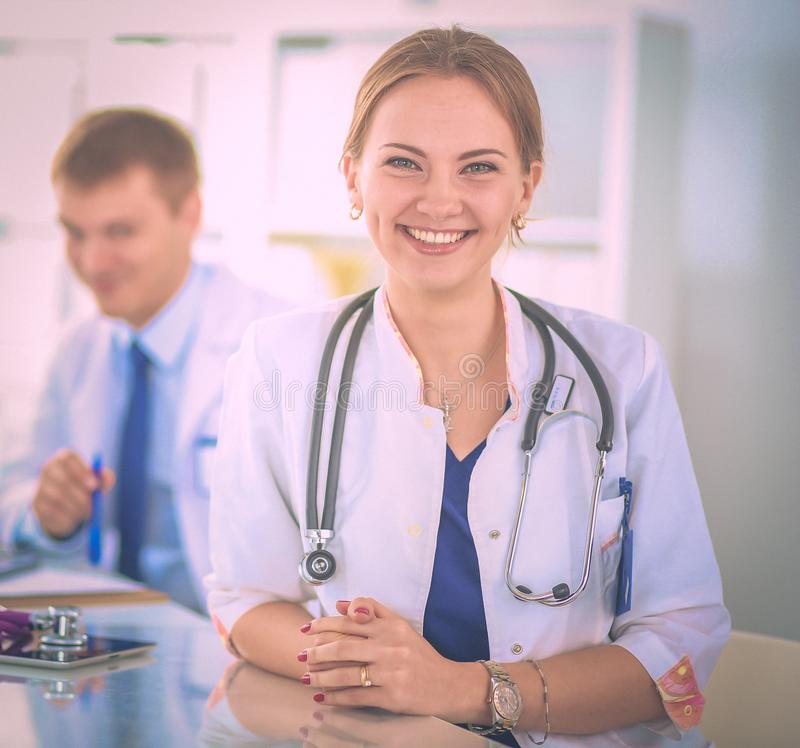 Beautiful young smiling female doctor sitting at the desk royalty free stock photo