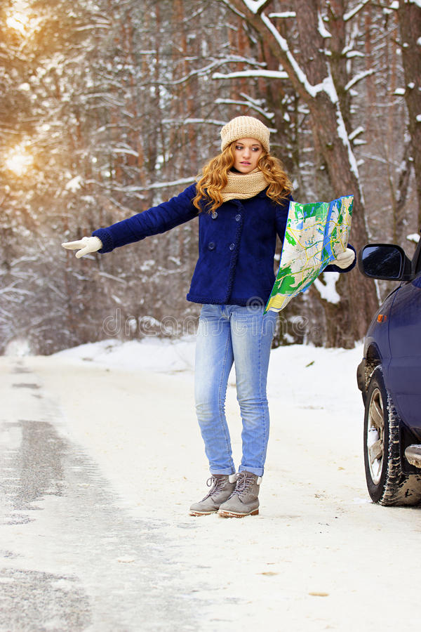 Beautiful young smiling girl hitchhiking on the highway with map in hand standing near a car, wearing blue jacket. Travel girl. Travel adventures of young royalty free stock images