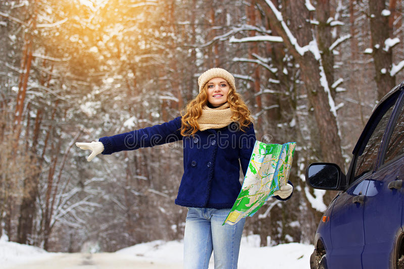 Beautiful young smiling girl hitchhiking on the highway with map in hand standing near a car, wearing blue jacket. Travel girl. Travel adventures of young royalty free stock image
