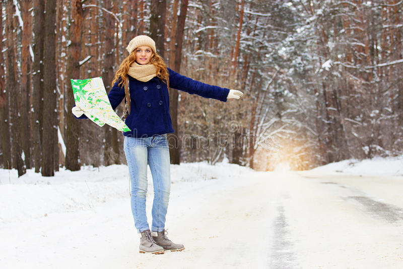 Beautiful young smiling girl hitchhiking on the highway with map in hand, wearing blue jacket and with bag on her back. Travel adventures of young, beautiful royalty free stock photos