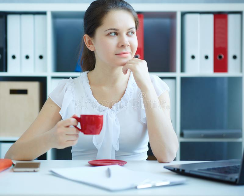 Beautiful young smiling thoughtful business woman holding cup of coffee. royalty free stock photos
