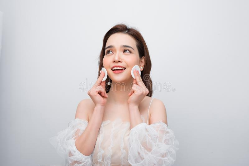 Beautiful young smiling woman with clean cotton pads . Facial treatment. Beauty skin care famale face . Expressive facial. Expressions royalty free stock image