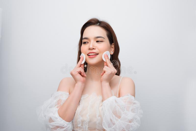 Beautiful young smiling woman with clean cotton pads . Facial treatment. Beauty skin care famale face . Expressive facial. Expressions royalty free stock photography