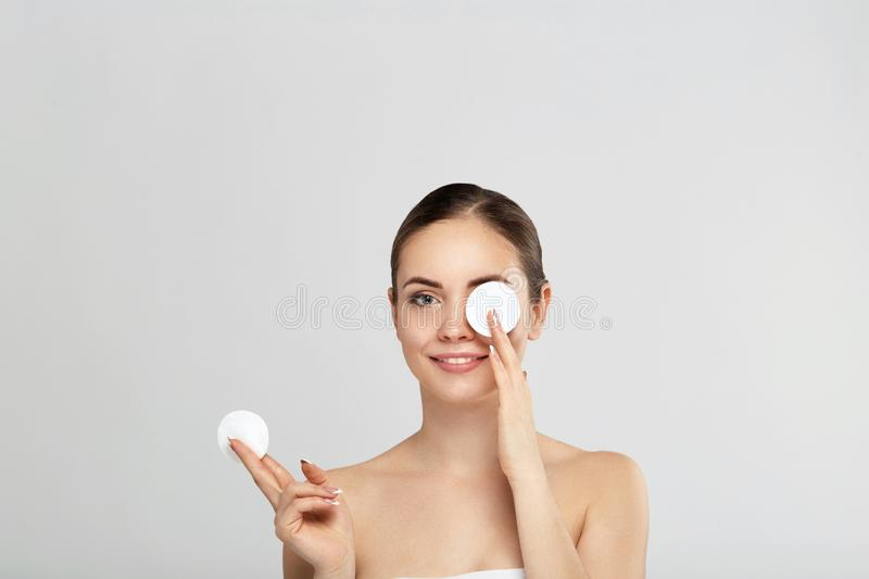 Beautiful young smiling woman with clean cotton pads . Facial treatment . Cosmetology , beauty and spa .Beauty skin care famale fa. Ce . Expressive facial royalty free stock image