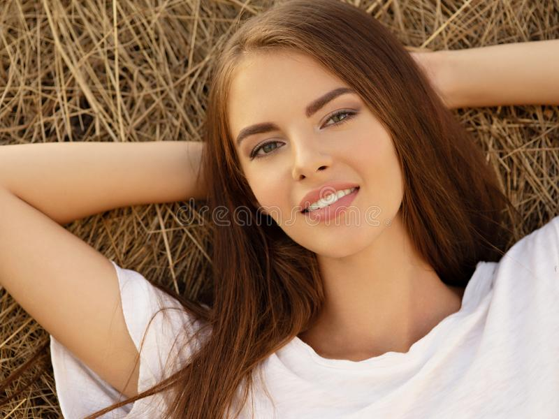 Beautiful young smiling woman is relaxing on the haystack. stock photography