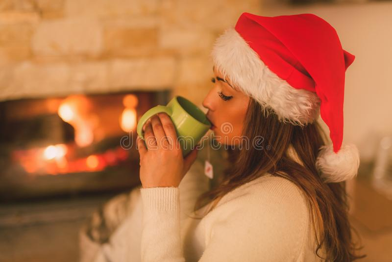 Enjoying By The Fireplace. Beautiful young smiling woman with santa hat enjoying a cup of tea by the fireplace royalty free stock photos