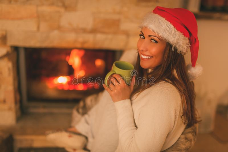 Enjoying By The Fireplace. Beautiful young smiling woman with santa hat enjoying a cup of tea by the fireplace. Looking at camera royalty free stock photos