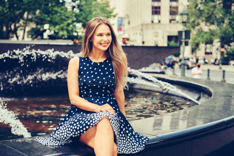 Beautiful young smiling woman sitting on city park fountain at summer day wearing dress and looking to the side stock image