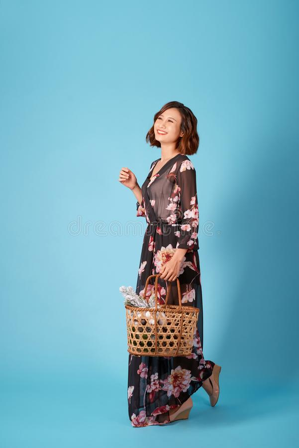 Beautiful young smiling woman in vintage dress holding a basket with flowers. Summer portrait pretty young girl royalty free stock images