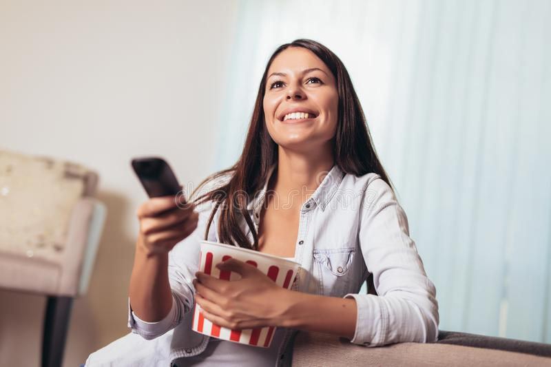 Young smiling woman watching a movie and eating popcorn royalty free stock image