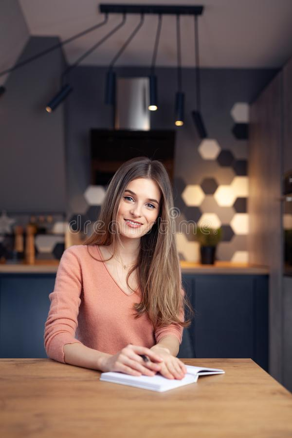 Beautiful young smiling woman working from home stock image