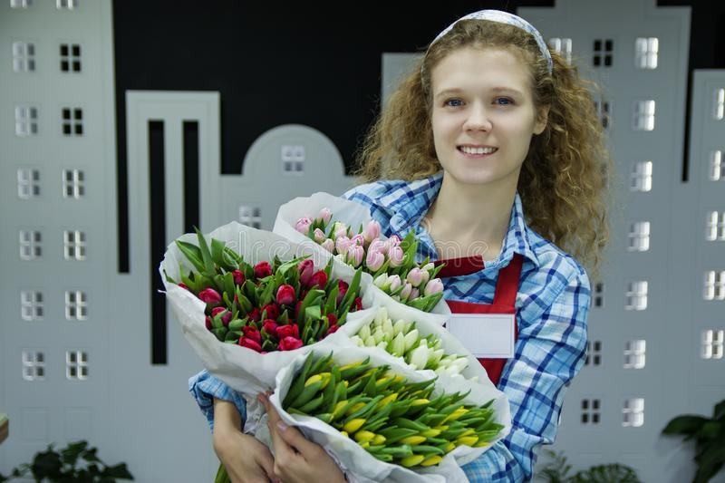 Beautiful young smilling woman florist are selling the bouqet of the tulips in flower shop royalty free stock image