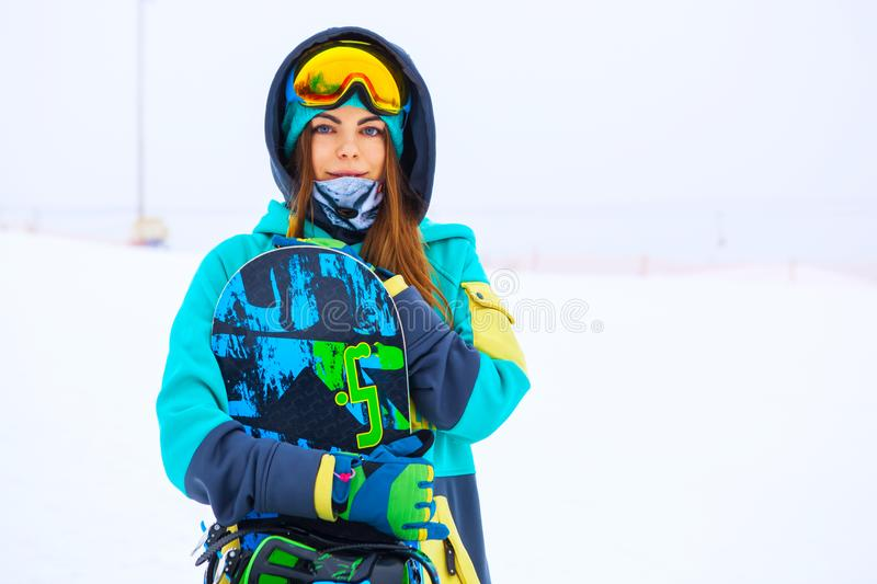 Beautiful young snowboarder girl holding snowboard. Portrait of beautiful young snowboarder girl holding snowboard stock photo