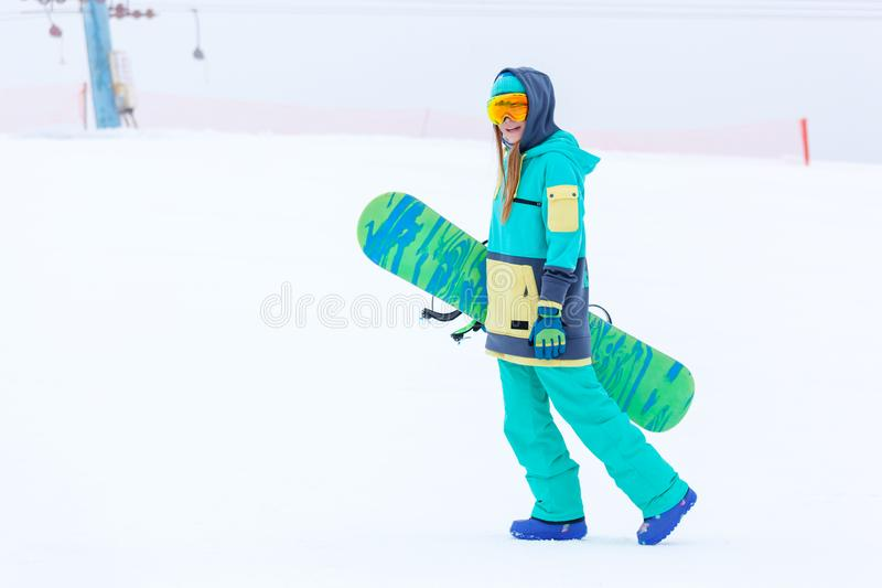 Beautiful young snowboarder girl holding snowboard. Portrait of beautiful young snowboarder girl holding snowboard royalty free stock photography