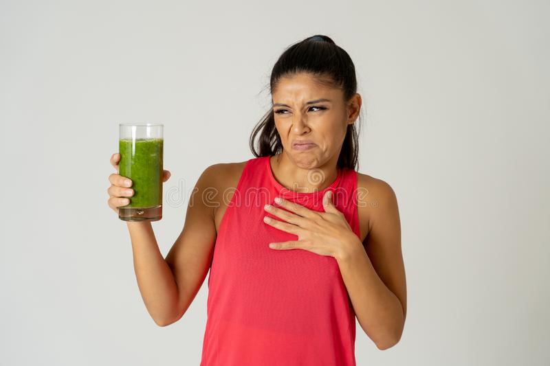 Beautiful young sport woman tired of diet holding green smoothie in dislike stock photo