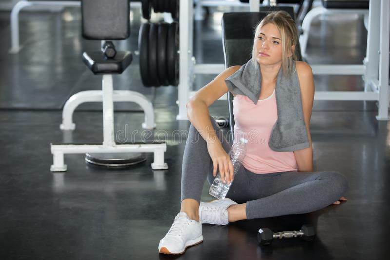 Beautiful young sport woman tired taking a break from  exercise sitting on floor drinking water and towel sweat and dumbbell in stock photo
