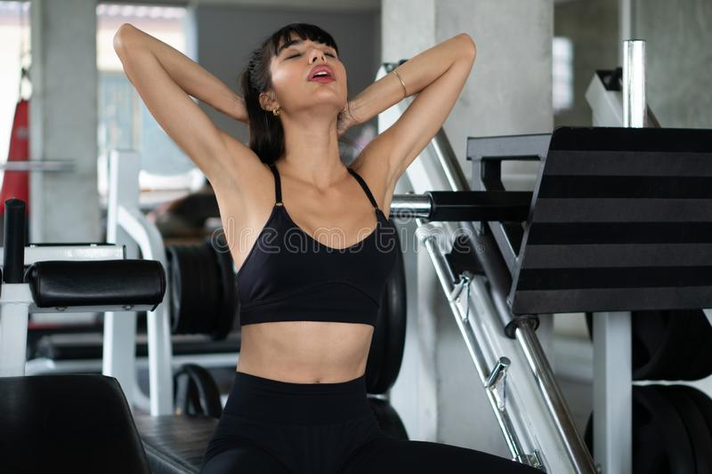 Beautiful young sport woman tired taking a break from exercise sitting on machine  in fitness gym . girl in sportswear workout. Rest . lady  stretching  arm and royalty free stock images