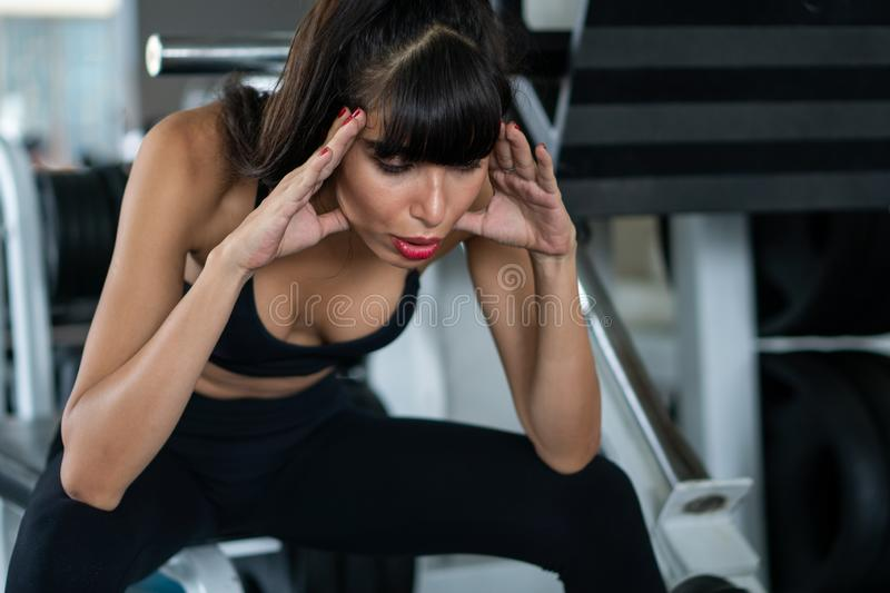 Beautiful young sport woman tired taking a break from exercise sitting on machine  in fitness gym . girl in sportswear workout. Rest . lady exhausted by over stock photography