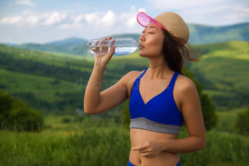 Beautiful young sports asian woman drinking water a refresh after torrid heat summer day in mountains. royalty free stock image