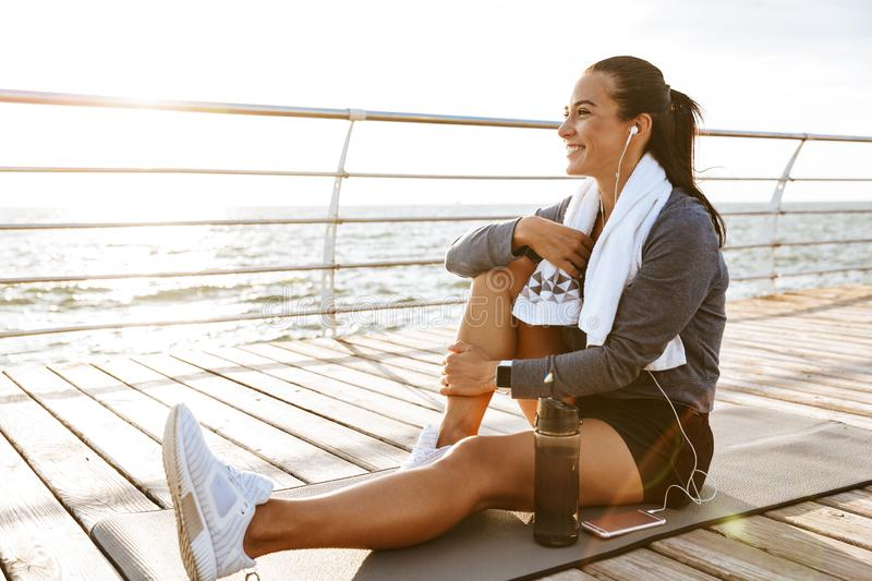 Beautiful young sports fitness woman have a rest at the beach outdoors listening music with earphones. Image of a beautiful young sports fitness woman have a stock images