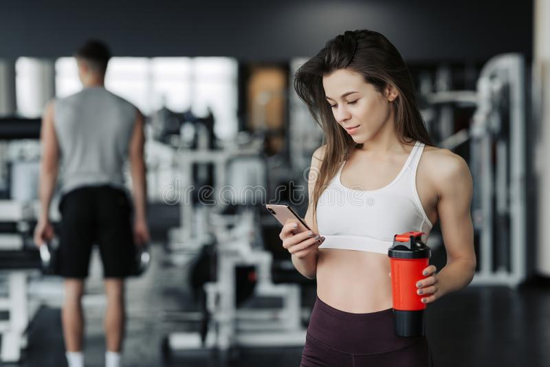 Beautiful young sportswoman in sportswear and earphones is holding a bottle of water, listening to music using a phone and smiling stock photo