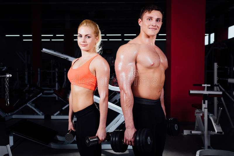 Beautiful young sporty couple showing muscle and posing with dumbbells in gym during photoshooting royalty free stock photography