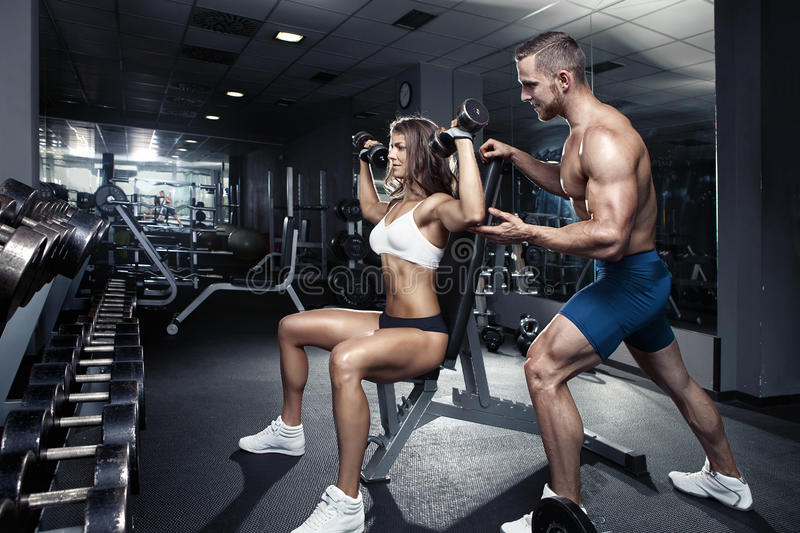 Beautiful young sporty couple in gym stock photography