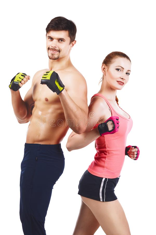 Beautiful young sporty couple showing muscle isolated on a white background. Athletic young fitness couple in sportswear posing over white royalty free stock images