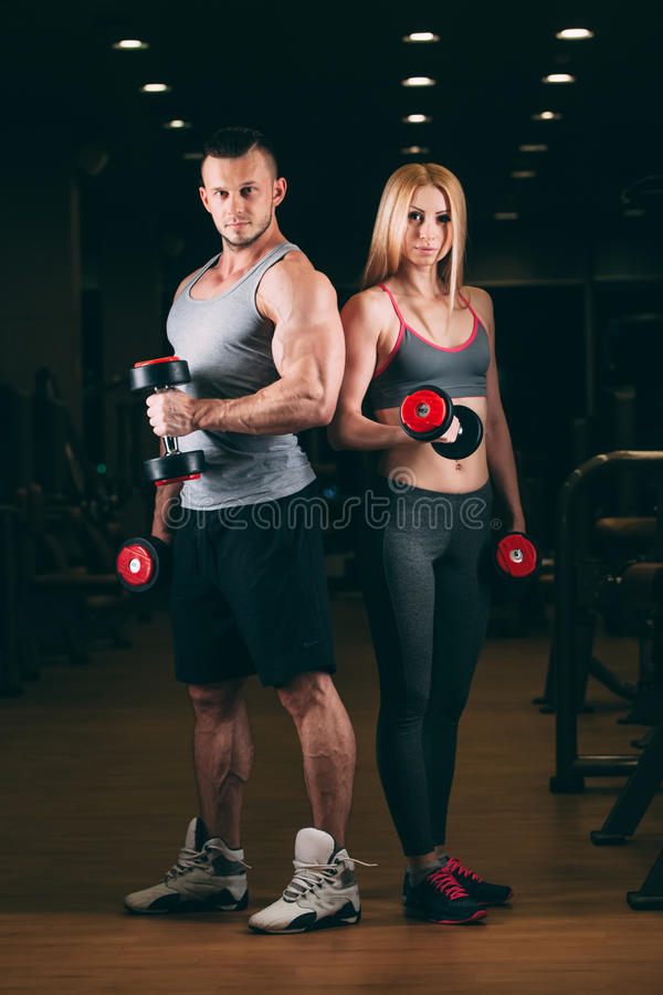 Beautiful young sporty couple showing muscle and workout in gym dumbbell stock photography