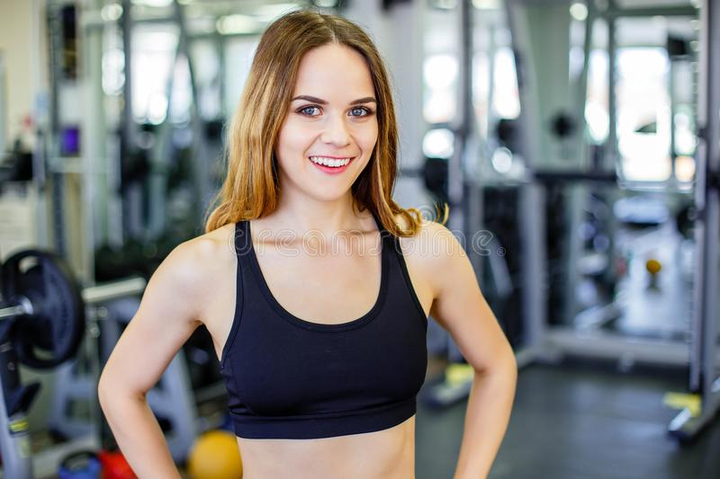 Beautiful young sporty woman. Fitness girl training in sport club with exercise equipments. Woman smiling and looking at camera. royalty free stock photo