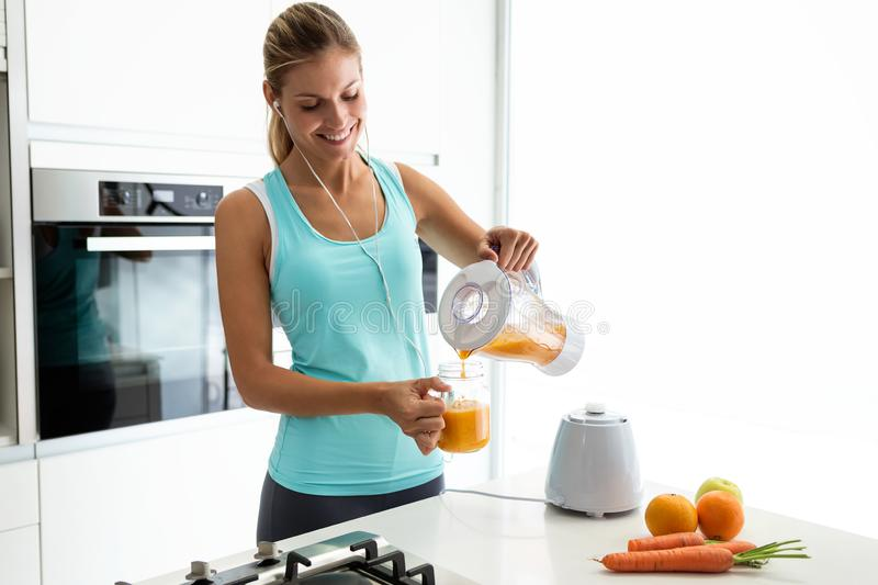 Beautiful young sporty woman serving detox orange juice into glass while listening to music in the kitchen. stock photo